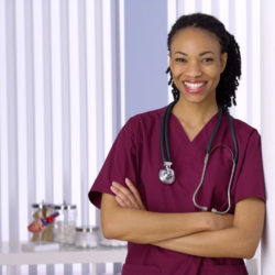 smiling black woman nurse with arms folded with stethoscope draped around neck area