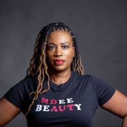 Diedre Smith of MDee BEauty looking strong and wearing tee-shirt with company name across it