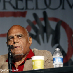 Civil Rights leader Bob Moses sits at podium table speaking in to microphone