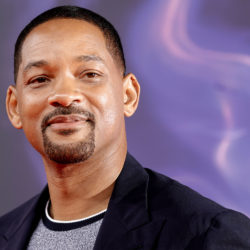 Will Smith pictured in front of a purple backdrop while smiling away from the camera