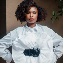 Jennifer Hudson standing with a white button up shirt with her arms on her hips.