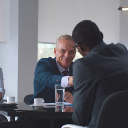 male board member at conference table skaes hands with black male others looking on