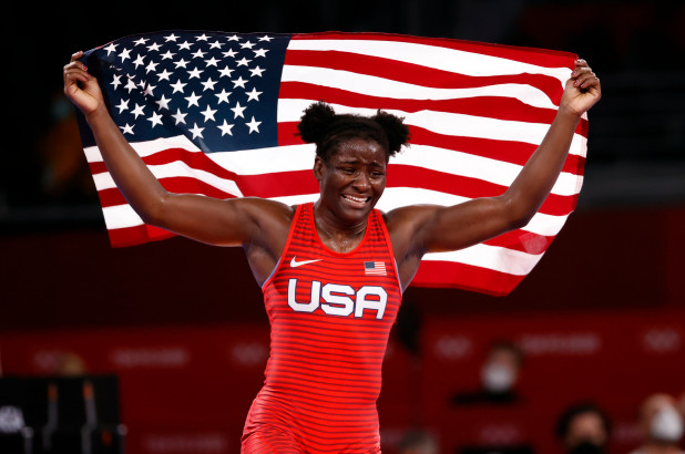 gold medalist holding up the american flag in wrestling uniform