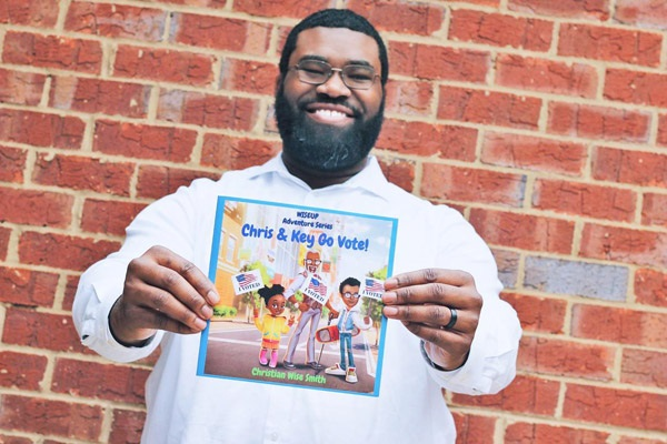 Christian Wise Smith, suthor, smiling and holding up his childrens book