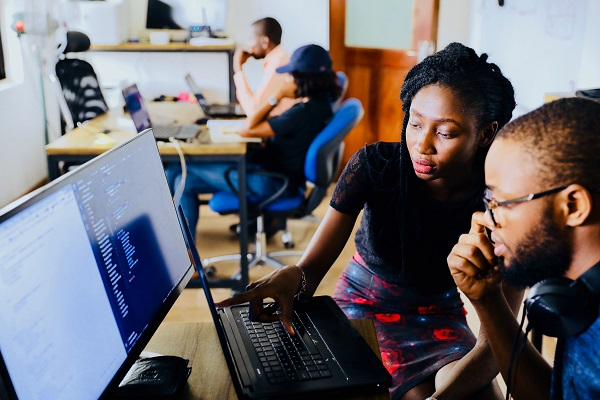 Young black male college student with black female teacher looking over computer graphic